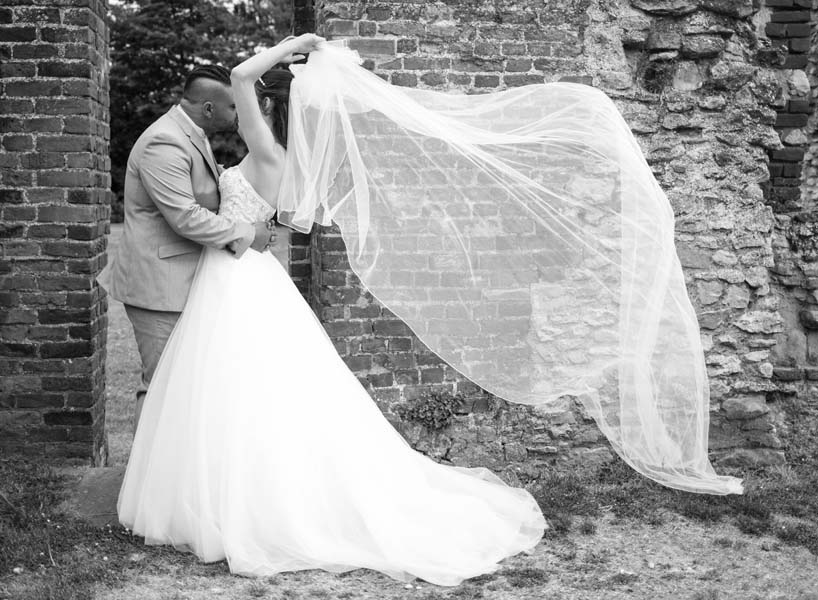 newlyweds kissing each other, wedding photographer in Enfield, Enfield photographer taking photos of bride and groom in Waltham Abbey Gardens, London, the vail is floating in the air