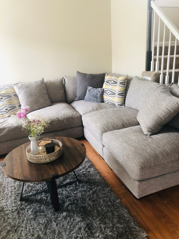 Cleaning living room with sectional and flowers