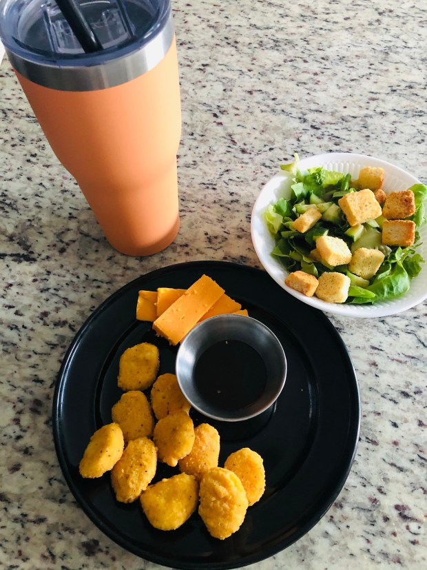 Chicken nuggets, cheese, salad, and water