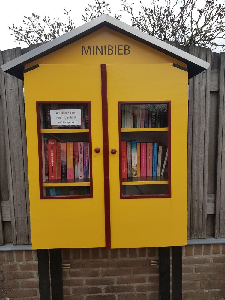 Er staat een gele kast op de foto, bovenaan de kast staat in hoofdletters MINIBIEB. De kast heeft een puntdak. Er zitten 2 deuren in de kast met ramen. Daardoorheen kun je veelkleurige boeken zien staan. Op het linker raam staat de tekst: 'Breng een boek. Neem een boek. Veel leesplezier.'