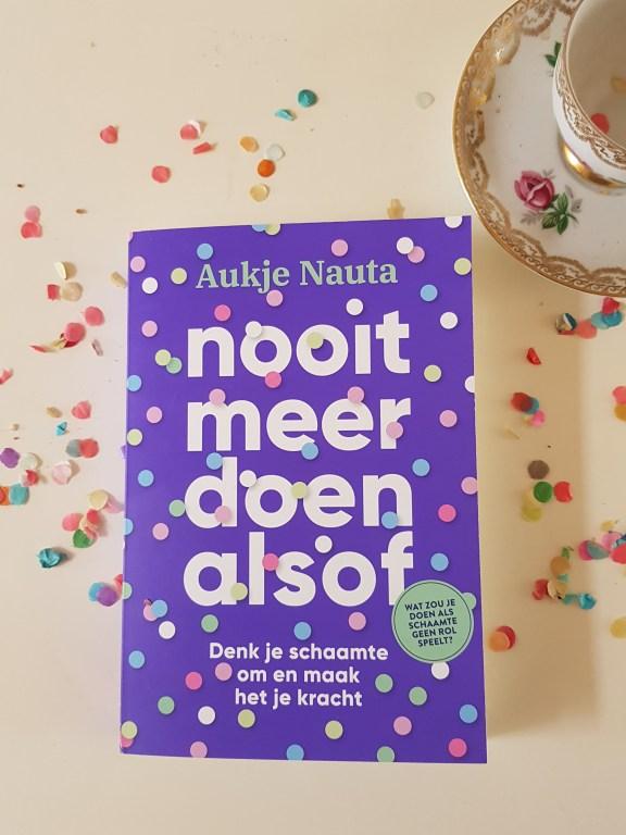 Op een witte achtergrond ligt het paarse boek 'Nooit meer doen alsof' van Aukje Nauta. Op de cover van het boek staat confetti. Om het boek heen ligt ook confetti en rechtsboven het boek staat een ouderwets theekopje met een gouden rand.