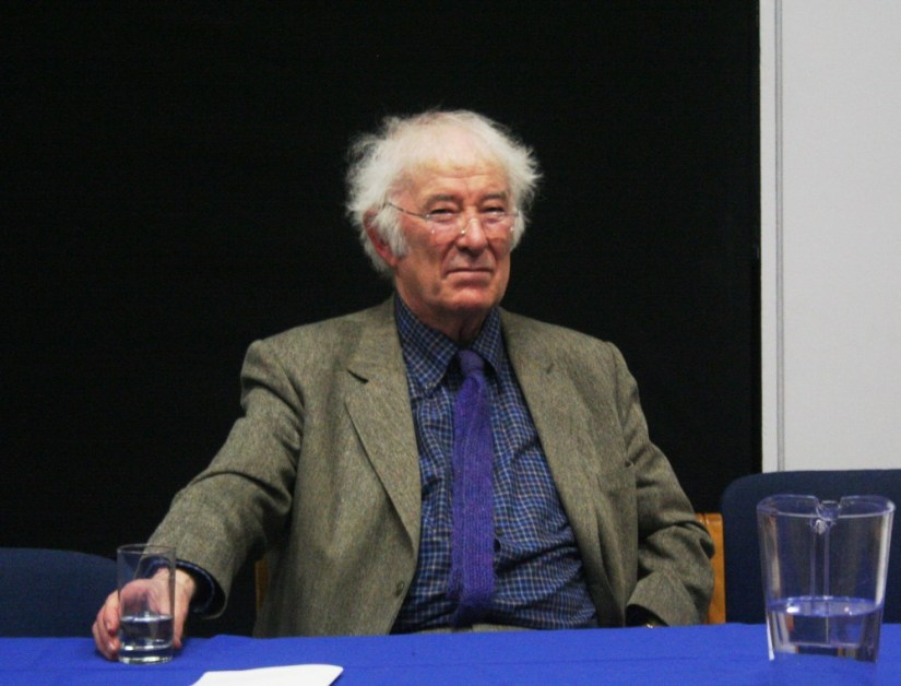 Seamus Heaney sitting at a table with a glass of water in 2009.