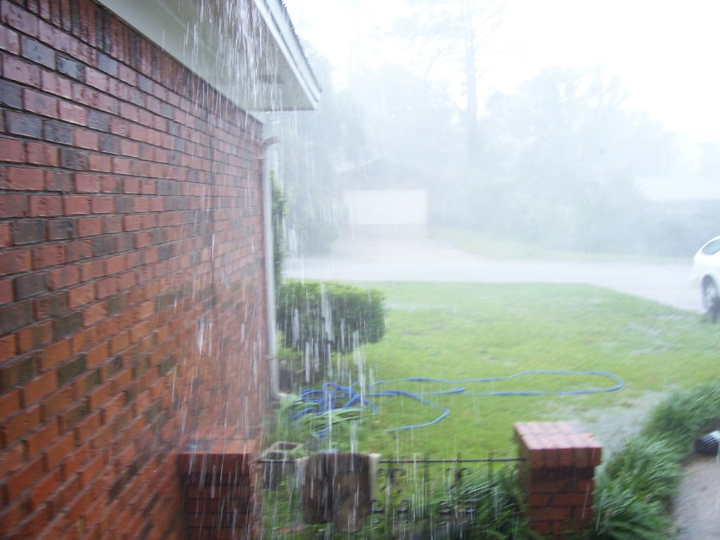 Rain pouring down side of brick house.