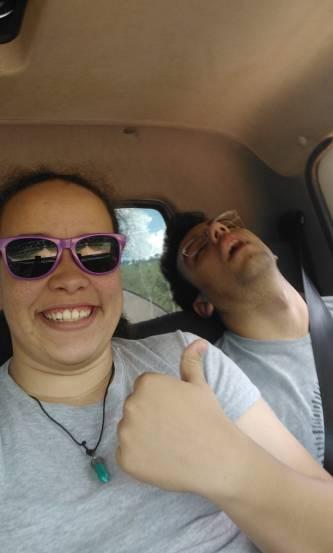 Ana rindo e apontando para o Gabriel dormindo no caminhão