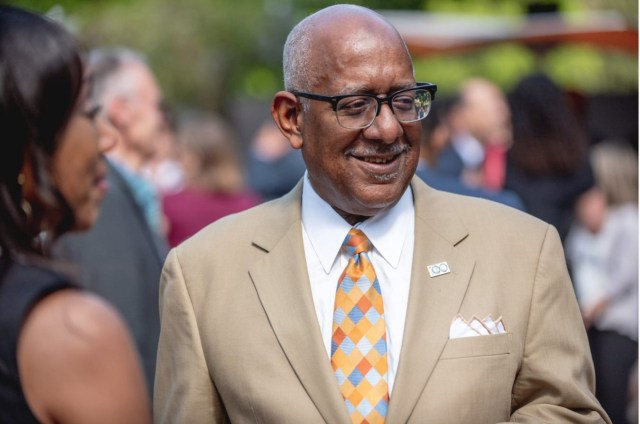 Allen Edson, Black man with glasses in light brown suit and orange/blue patterned tie standing and smiling in the crowd.
