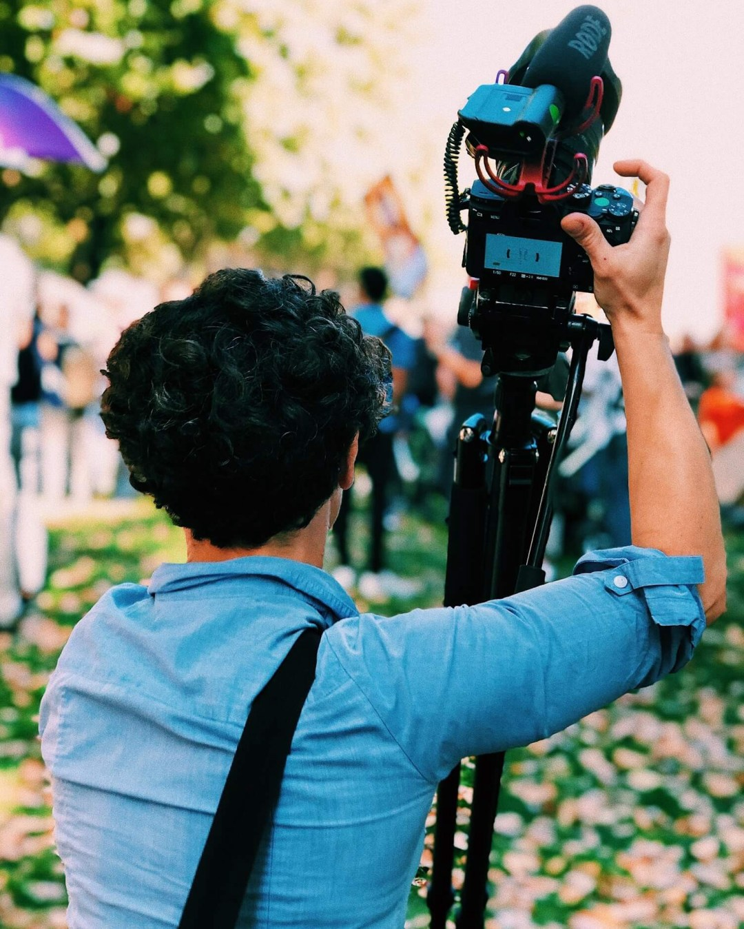 Journalist wearing a blue shirt and holding a camera during a live event on a garden.