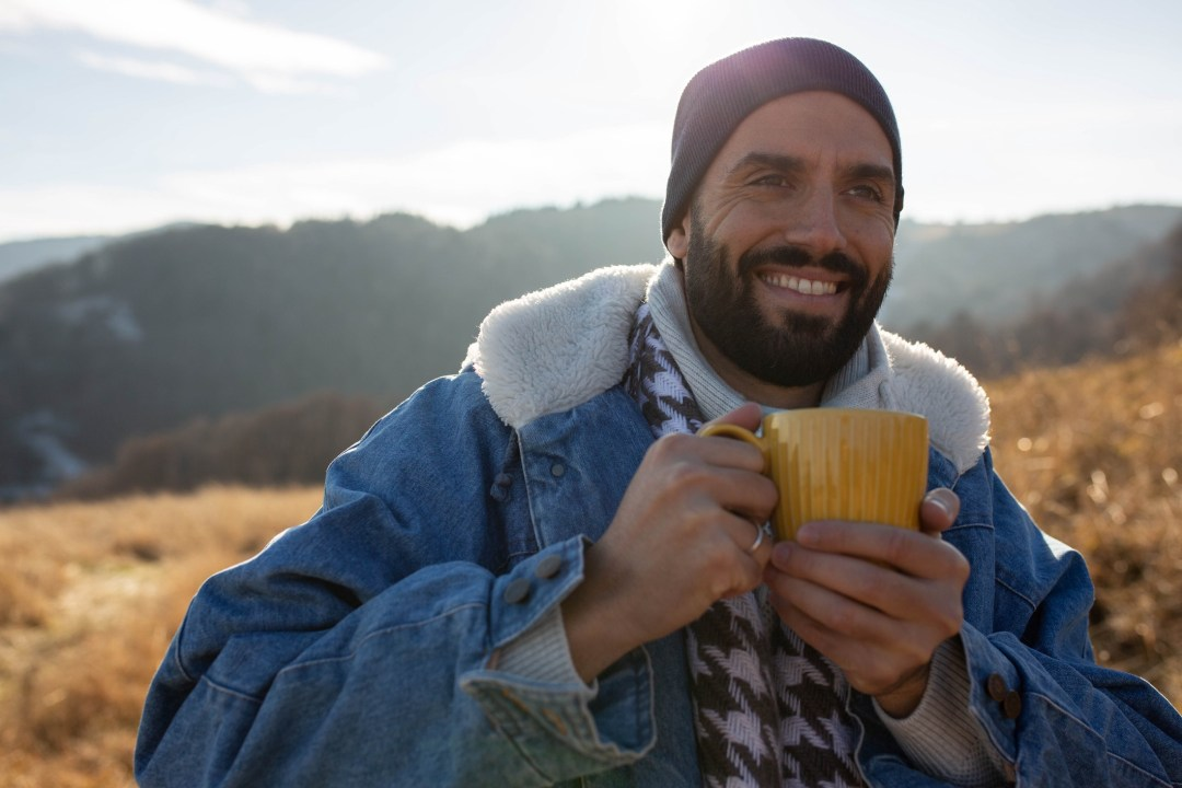 A man drinks a hot beverage while dressed warmly out in an open field.