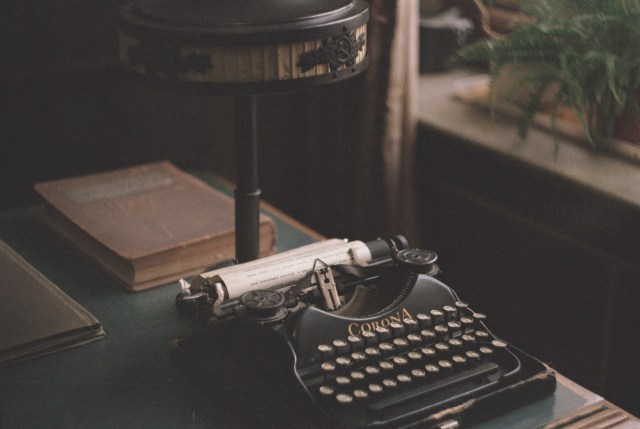 A dimly lit room with an old typewriter on the desk and plants on a faraway table