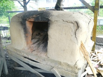 The oven is located in the yard and is a structure made of mud, cow patties (dried cow poop), and water mixed together in a manner reminiscent of an adobe-like square structure.