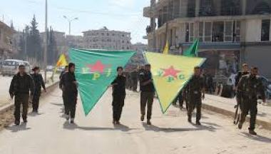 Soldiers holding YPG and YPJ banners.