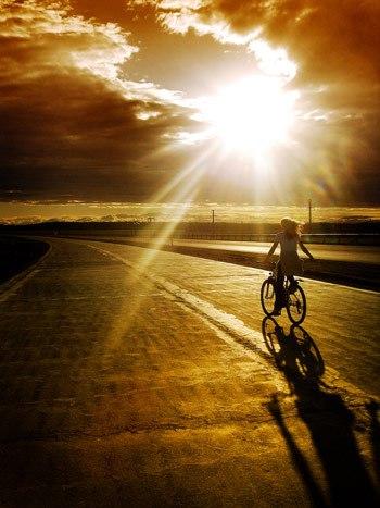 joyful woman riding a bike at sunset