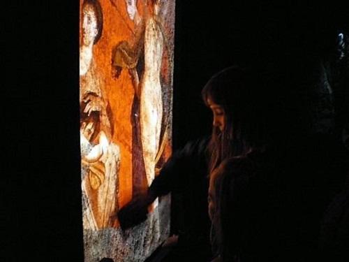 Niña interaccionando con pantalla en el museo virtual de Herculano