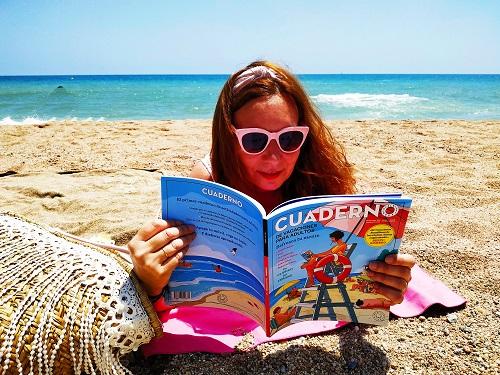 Chica en la playa con el cuaderno de vacaciones para adultos