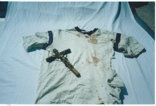 Camiseta manchada de sangue e cruz de Nivaldo