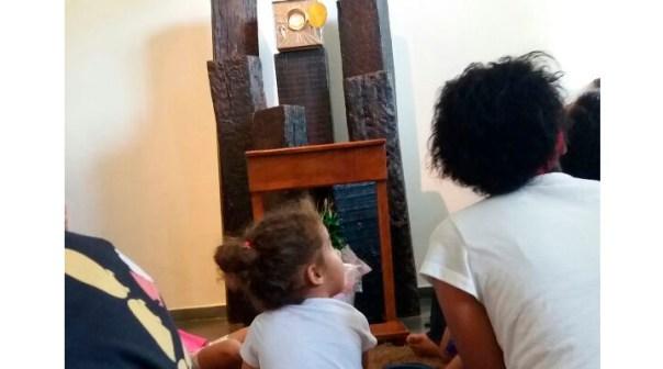 Criança na capela adora a Eucarístia