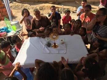 Crianças adoram a Cristo na eucaristia em missão São Felipe Neri