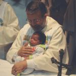 Padre João Henrique segura uma criança