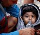 voluntária dá água para criança