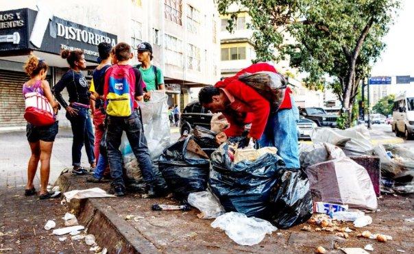 pobre revira lixo a procura de alimento.