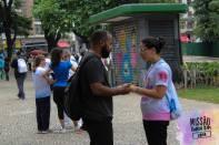 Jovem missionário ora com um pedestre.