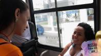 Mulher sorri ao ser abordado por missionários nos ônibus.