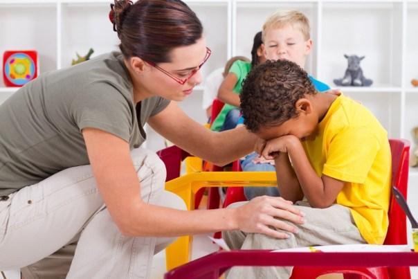 Professora consola um aluno em sala de aula