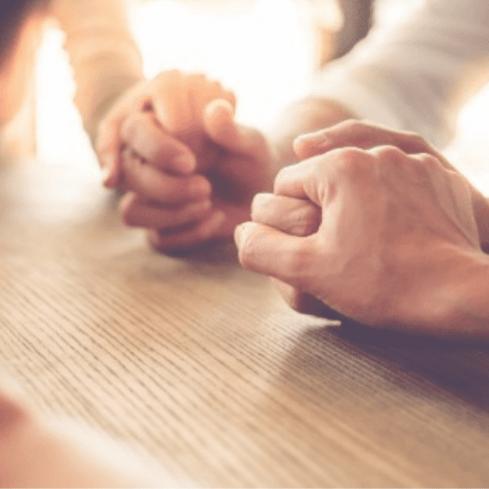Pessoas oram de mãos dadas