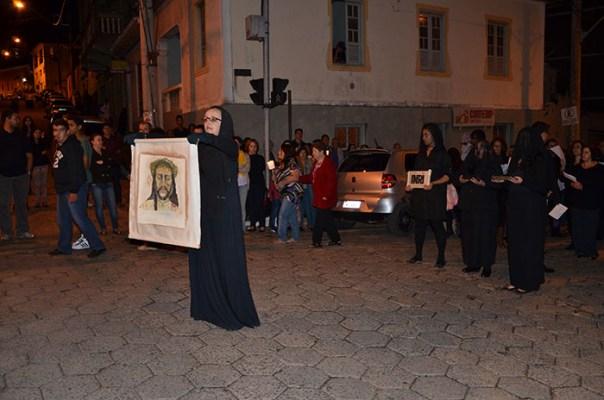 Mulher representando Verônica, canta e mostra um tecido com o face de Cristo.