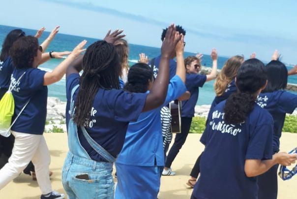 Jovens cantam na orla da praia da Caparica.
