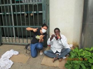 Missionária durante entrega de alimentos a irmão em situação de rua, em BH
