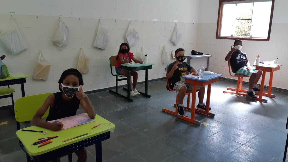 Crianças na sala de aula com distanciamento social.
