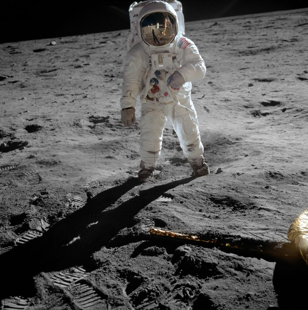 """Astronaut Buzz Aldrin on the moon Full description: Astronaut Buzz Aldrin, lunar module pilot, stands on the surface of the moon near the leg of the lunar module, Eagle, during the Apollo 11 moonwalk. Astronaut Neil Armstrong, mission commander, took this photograph with a 70mm lunar surface camera. While Armstrong and Aldrin descended in the lunar module to explore the Sea of Tranquility, astronaut Michael Collins, command module pilot, remained in lunar orbit with the Command and Service Module, Columbia. This is the actual photograph as exposed on the moon by Armstrong. He held the camera slightly rotated so that the camera frame did not include the top of Aldrin's portable life support system (""""backpack""""). A communications antenna mounted on top of the backpack is also cut off in this picture. When the image was released to the public, it was rotated clockwise to restore the astronaut to vertical for a more harmonious composition, and a black area was added above his head to recreate the missing black lunar """"sky"""". The edited version is the one most commonly reproduced and known to the public, but the original version, above, is the authentic exposure. A full explanation with illustrations can be seen at the Apollo Lunar Surface Journal."""