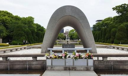 """Blick durch den Kenotaph auf die Flamme des Friedens und den """"Atomdom"""""""