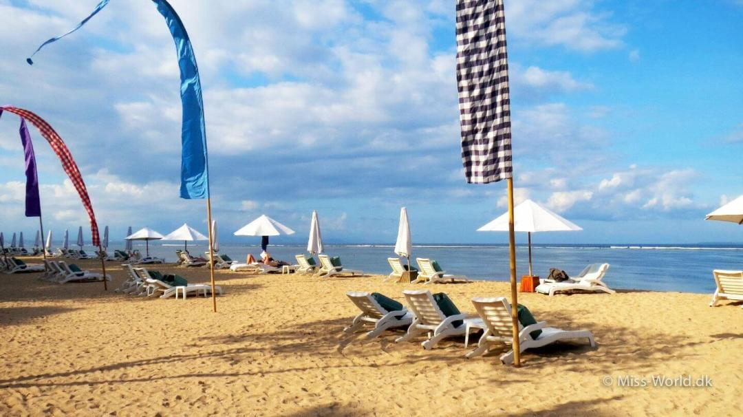 Sun chairs and flags at the peaceful Sanur Beach Bali