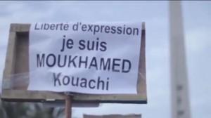 Um dos cartazes levantados em Dakar. Obelisco de Dakar ao fundo