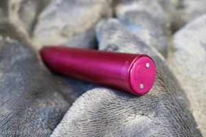 Picture of the Blush Novelties Exposed Nocturnal Lipstick Bullet Vibrator (a dark pink lipstick shaped vibrator), all set on a backdrop of a grey blanket.