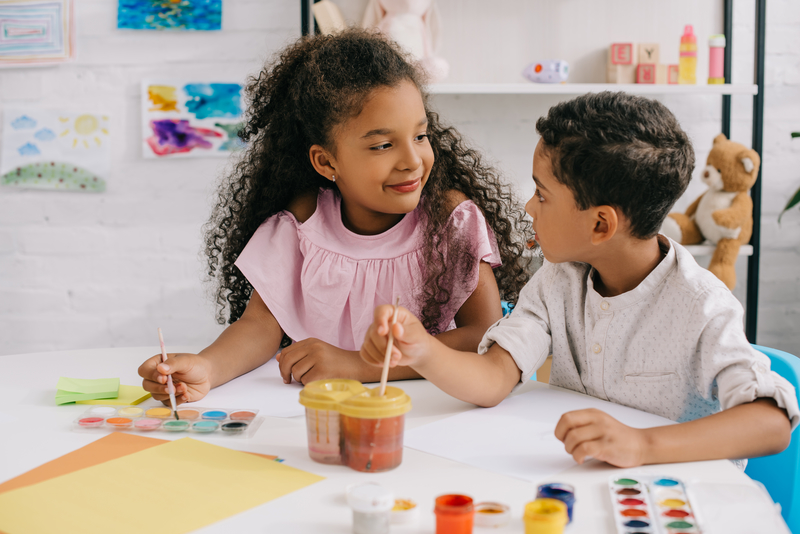 african american kids while looking at each other whdrawing pictures with paints and paint brushes in classroom