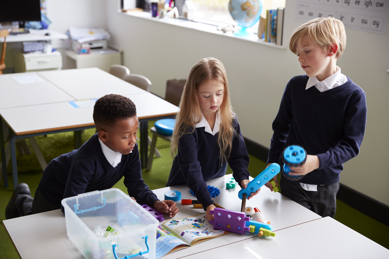 Elevated view of three primary school kids standing at a table in a classroom, working together with toy construction blocks