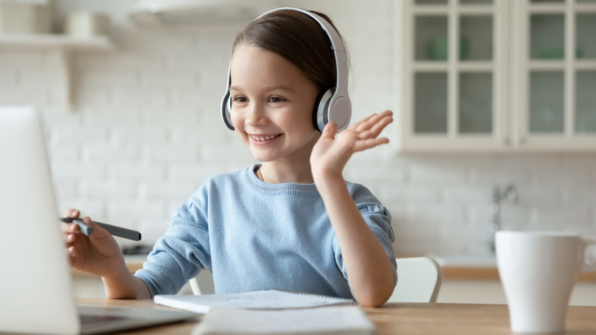 Bambina con cuffie che fa i compiti