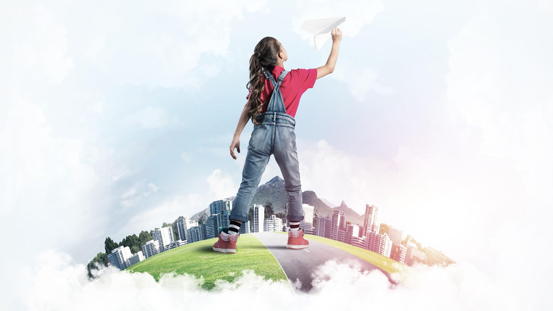 Bambina che lancia aeroplano di carta con città sullo sfondo