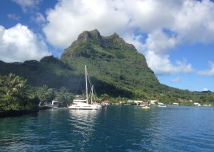 6. Joyful docked on the far side of a catamaran in Bora Bora.  You can see Joyful' hull, mast and two headsails just beyond the big catamaran's rigging. Mt. Pahia is in the distance, which sheltered Joyful from the prevailing Easterly winds.