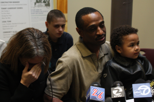 Tracey Washington(left) sits next to her husband Charles Washington as he speaks to reporters.