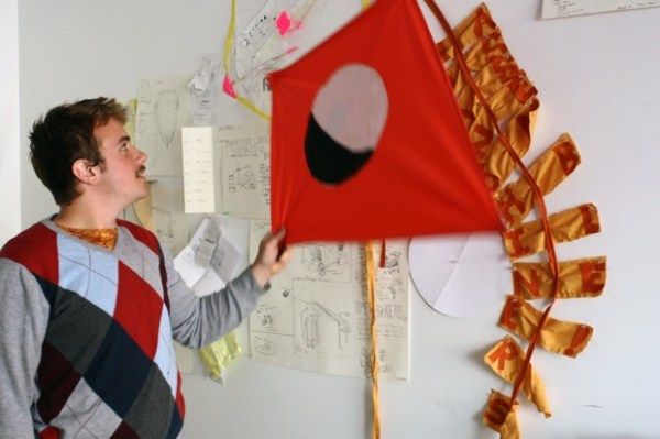 """A kite made by Cox and Allende. The tail spells out """"Moonshiners Assemble"""" The image on the kite is of a waxing moon."""
