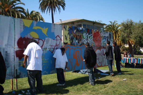 Several youth at the community wall.