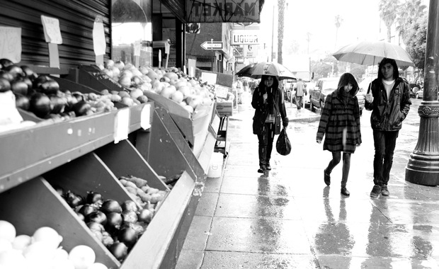 Pedestrians traverse the rainy street under hood and umbrellas.