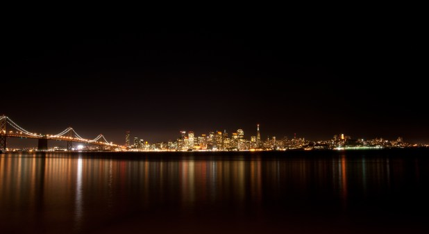 San Francisco glows orange across the water, seen from Treasure Island.