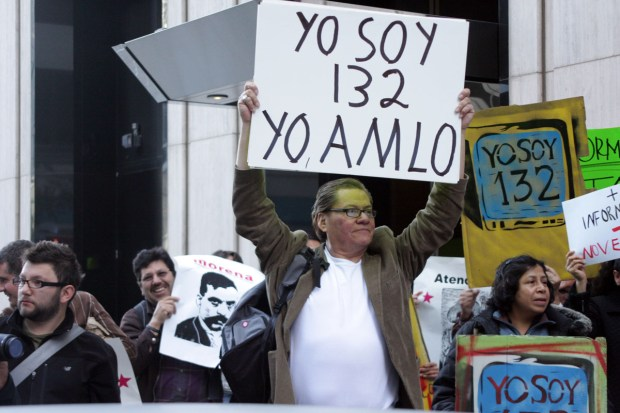 Demetrio Flores of San Francisco holds a sign in front of Univision's San Francisco offices..