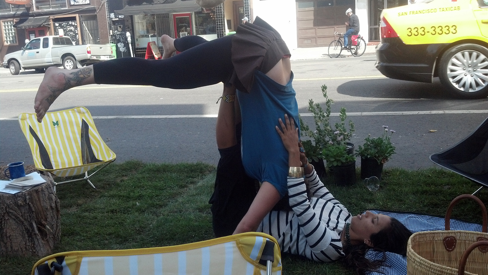 A young woman gives another young woman a human airplane ride at a pop-up parklet.