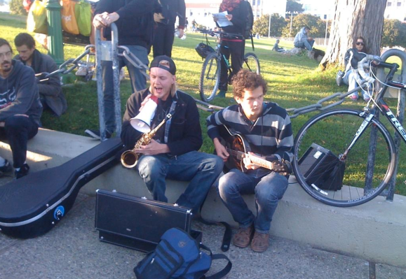 "A few protesters perform the song ""Come Together"" by The Beatles. Photo by Carly Nairn."