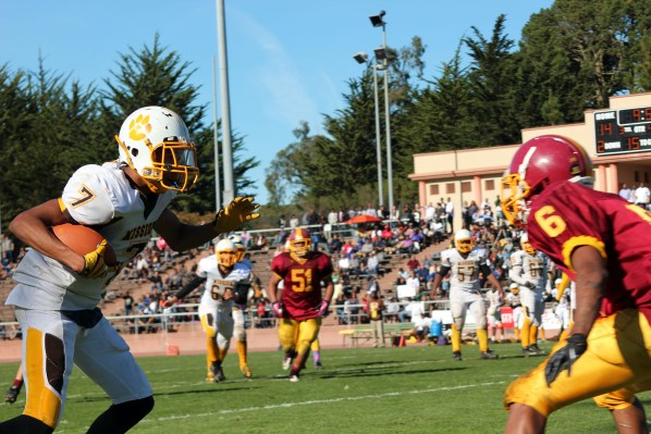 Wide receiver Demitrius Thibeaux negotiates a run past a Lincoln High defender on Turkey Day.